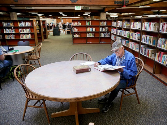 Paul Moses looks for information as he researches his Port Orchard home during World War II at the Kitsap Regional Library Sylvan Way branch on Monday. The library is going to invest in new furniture if the levy passes.