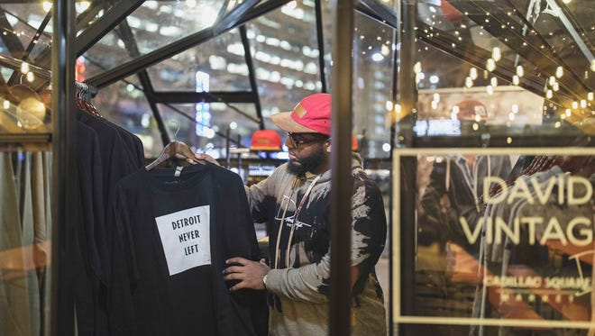 David Vintage, founder of Joseph David, prepares his Detroit-inspired haute couture line at the Cadillac Square Market.