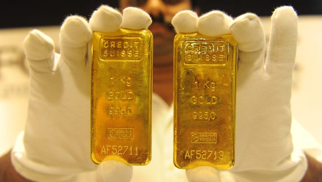 A jewelry shop employee displays 24-carat gold bars in Ahmedabad on August 20, 2011.  (Photo: SAM PANTHAKY/AFP/Getty Images)