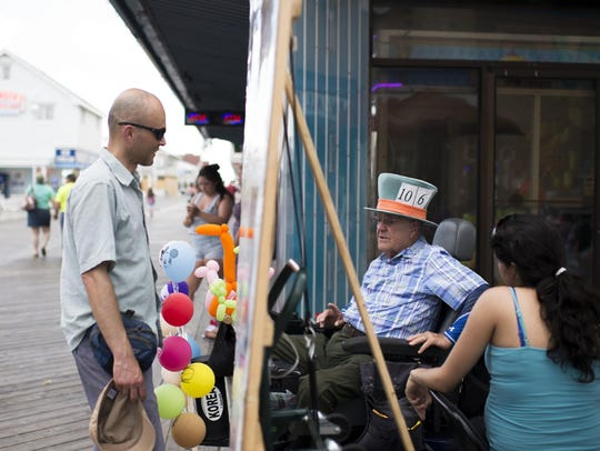 """William Campion, center, sells balloons as the """"Mad"""