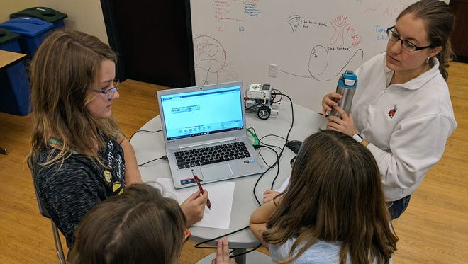 Laura Lauer looks on as a group solves a problem during a TechWise Academy middle school robotics class.