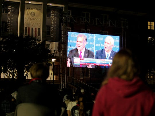 Students and visitors watch the outside broadcast of the vice presidential debate on Stubbs Mall at Longwood University on Tuesday, Oct. 4, 2016 in Farmville, Va.