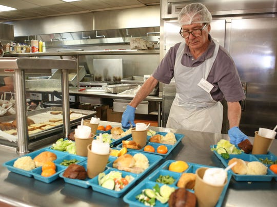 Volunteer Gordan Girvan serves meals at Martha's Village and Kitchen in Indio during the lunch hour, Thursday, March 23, 2017.