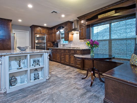 This kitchen is every person's dream with granite countertops, custom made cabinets, stainless steel appliances, gas range cooktop, beautiful tile backsplash, banquette seating and a huge island perfect for entertaining guests