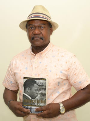 """Craven County Commissioner Theron McCabe holds his signed copy of the book """"Walking with the Wind: A Memoir of the Movement,"""" the late US Representative and Civil Rights icon John Lewis's account of his early years in the Civil Rights Movement."""