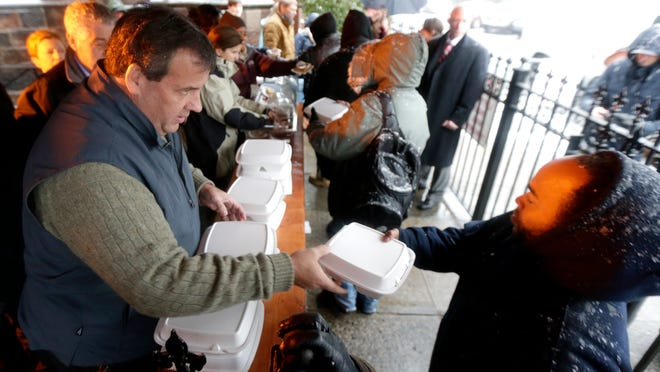 """New Jersey Gov. Chris Christie, left, hands a pre-Thanksgiving meal to a person at the St. John's Church soup kitchen, Wednesday, Nov. 26, 2014, in Newark, N.J. Members of the Christie administration have been participating in their fourth annual """"Season of Service"""" by volunteering around the state. Cabinet members this week have been sorting, packaging and serving holiday meals for various food pantries. (AP Photo/Julio Cortez)"""