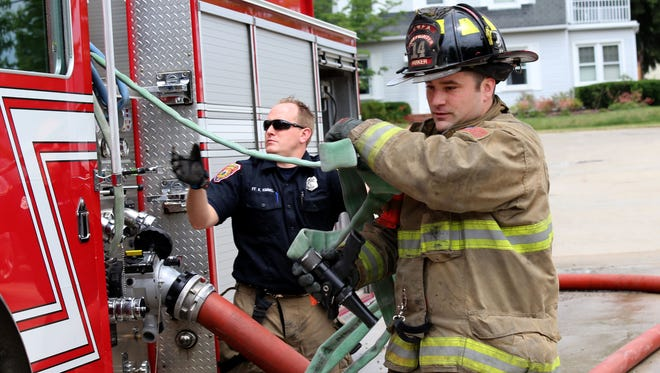 Firefighter Steve Parker pulls out a 1.5 inch hose from the fire truck as Senior Fire fighter Kevin Kimmel assists  during a training exercise in the back of the City of Wayne Fire Station 5 on Thursday, June 23, 2016.