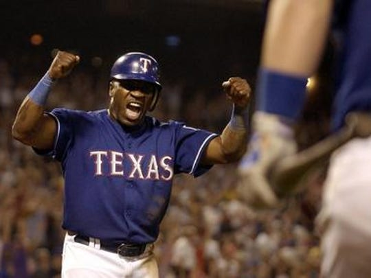 The Texas Rangers' Eric Young (left) celebrates as he crosses home plate on a Michael Young single in the 10th inning to give the Rangers a 16-15, come-from-behind win over the Detroit Tigers, Saturday, May 8, 2004, in Arlington, Texas.