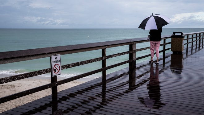 Tourists braved the rainy weather with the help of umbrellas at the Naples Pier on Sunday, May 20, 2018.