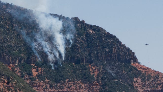 A helicopter is flown towards smoke and flames rising from a cliff on the face of Pine Valley Mountain Thursday, Sep. 10, 2015. Officials now estimate the size of the fire at 770 acres.
