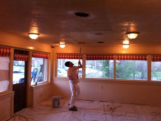 Joe Waddell paints the ceiling at 4141 Old Hillsboro