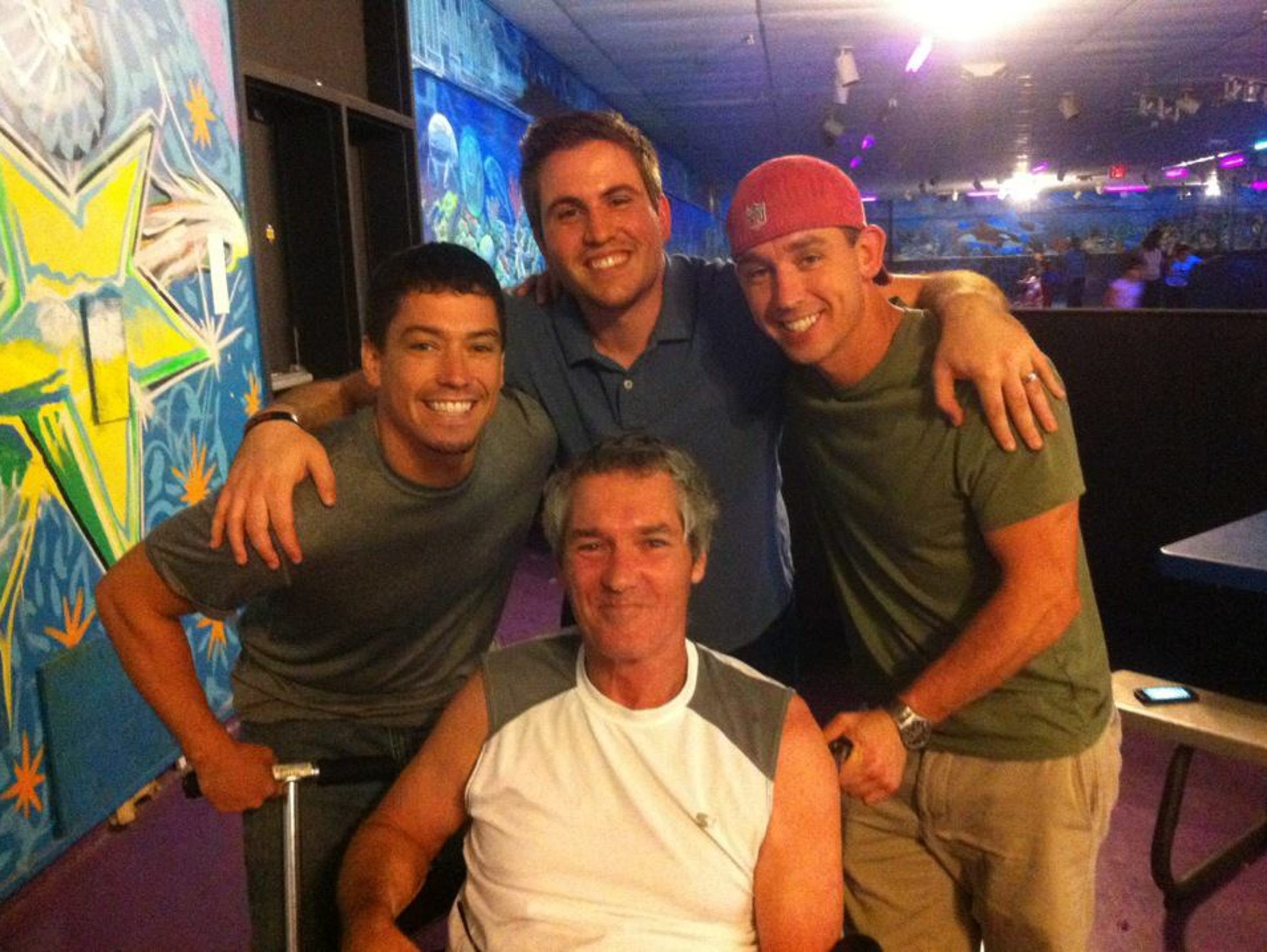 Christopher York, seated center, with his two sons and son-in-law at a skating rink. The photo was taken before he was hit by a car and had his leg amputated.