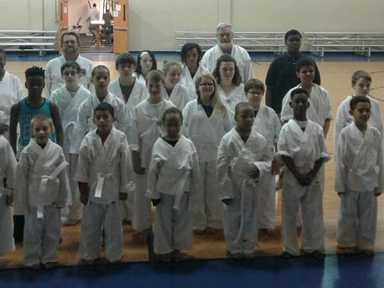 Students enrolled in the free Tuesday-Thursday taekwondo program receive their yellow belt recently.