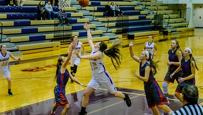 Jackie Jarvis ,center, of Fowlerville splits Maso defenders to lay the ball in putting Fowlerville up 42-40 with 36 seconds remaining in their game Tuesday January 3, 2017 in Fowlerville. KEVIN W. FOWLER PHOTO
