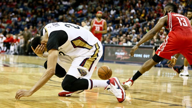 New Orleans Pelicans forward Anthony Davis (23) goes to the floor after taking an elbow to the head during the second quarter of a game against the Houston Rockets at the Smoothie King Center.