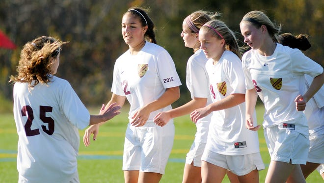 Arlington High Schools Jenny Caoili, center left, receives congratulations after scoring against Port Chester on Saturday in Freedom Plains. Oct. 25, 2014