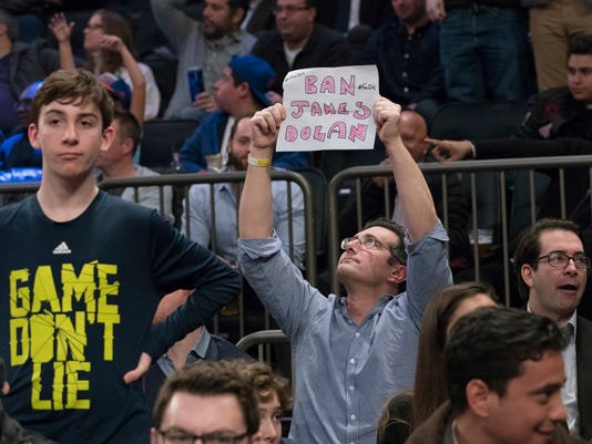 """A New York Knicks fan holds a """"Ban James Dolan"""" sign during the second half of an NBA basketball game between the Knicks and the Denver Nuggets, Friday, Feb. 10, 2017, at Madison Square Garden in New York.The Nuggets won 131-123. (AP Photo/Mary Altaffer)"""