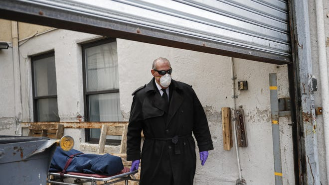 "Funeral director Tom Cheeseman wears personal protective equipment due to COVID-19 concerns as he collects a body from a nursing home, Friday, April 3, 2020, in the Brooklyn borough of New York. ""We took a sworn oath to protect the dead, this is what we do,"" he said. ""We're the last responders. Our job is just as important as the first responders."""