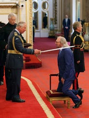 Barry Gibb is knighted by Prince Charles at investiture