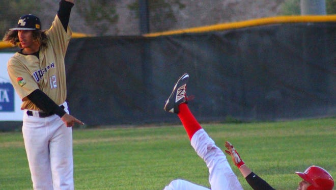 Aaron Olivas, left, appeals a pick-off attempt to the umpire Friday night at the Griggs Sports Complex.