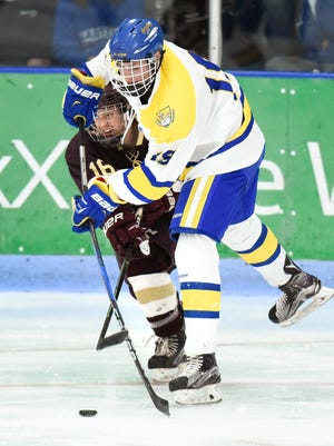 Cathedral's Michael Spethmann passes the puck past Fergus Falls' Logan Wentworth during the second period Saturday, Feb. 25, at the Municipal Athletic Complex.
