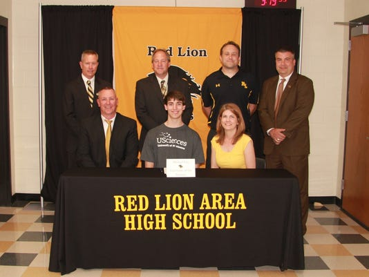 Red Lion's Mike Fox (center at table) signing his letter of intent to play basketball at the University of the Sciences. Fox is flanked by parents, John and Bonnie Fox. Back Row.  Arnie Fritzius, director of athletics;  Dr. Scott Deisley, Superintendent;  Steve Schmehl, head coach;  Mark Shue, principal