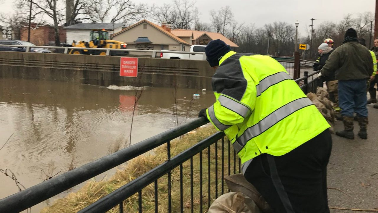 Firefighters and police in Eaton Rapids lay sandbags off Main Street on the banks of Springbrook.