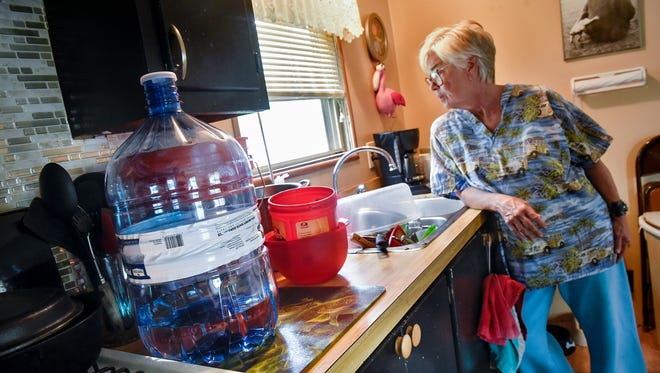Barbara Durham stands in her kitchen next to a bottle of water and the containers she is using to wash dishes in her home Monday in Sartell. Durham is a resident of Sartell Mobile Home Park, where some residents have been without water since Thursday due to a water line break.
