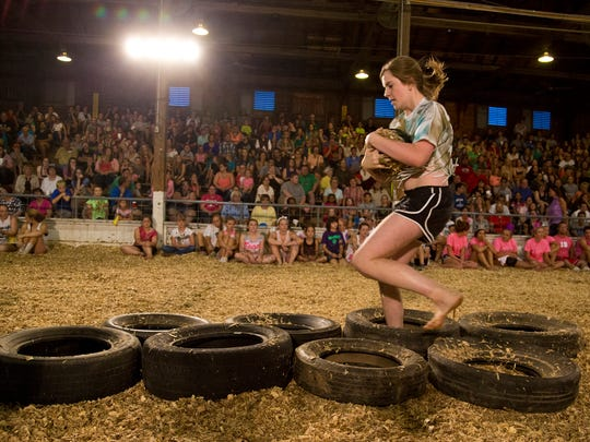 Rylie Miller tackles the tires during the 36th annual Greased Watermelon contest Thursday, July 24, 2014, at the Tippecanoe County 4-H Fair in Lafayette.