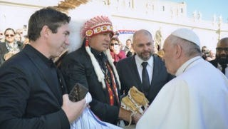 Charles Robinson, middle, gives moccasins to Pope Francis, right, as a gift.