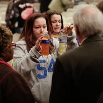 LeeAnne Walters, 36, of Flint shows water samples from her home to Flint emergency manager Jerry Ambrose on Wednesday after city and state officials spoke during a forum that addressed growing health concerns about the drinking water.