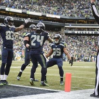 Seattle Seahawks running back Marshawn Lynch (24) celebrates with wide receiver Ricardo Lockette (83) and wide receiver Doug Baldwin (89) after scoring a touchdown against the Green Bay Packers during the second half in the NFC Championship game at CenturyLink Field.