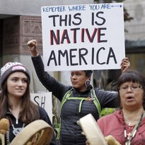 This October 2015 file photo shows Ruth Sims, a Navajo/Oglala Sioux, holds a sign during a demonstration for Indigenous Peoples Day, Monday, Oct. 12, 2015, in Seattle.