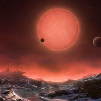 This artist's rendering shows an imagined view from the surface of the outermost of the three planets. The planet's sun and the other two planets are seen in the sky.