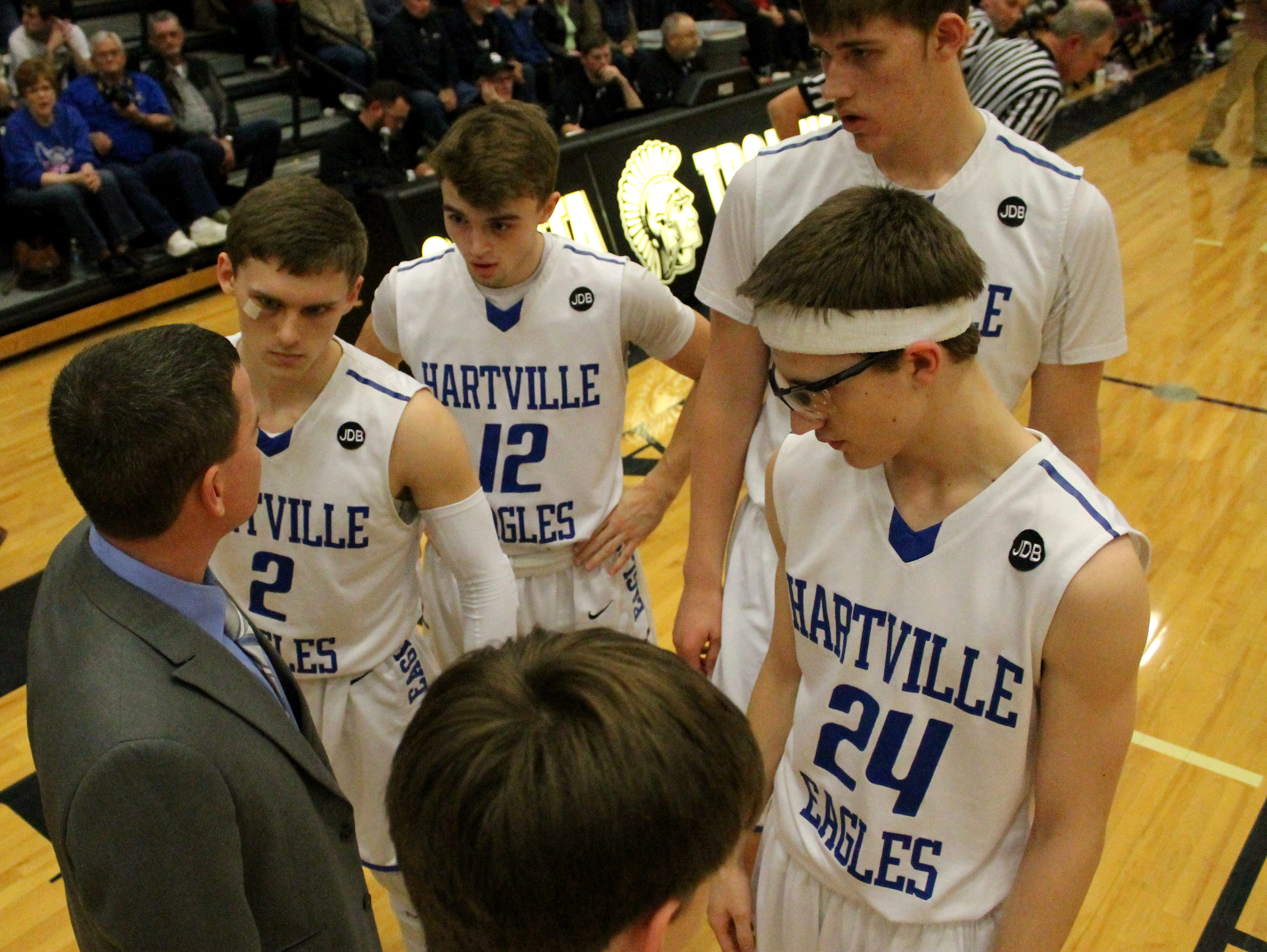 The Hartville High School boys basketball starting five gathers around coach Brett Reed moments before playing the 2017 Class 2 District 4 championship game against Mansfield at Sparta High School on Friday, Feb. 24, 2017. Pictured, from left, Reed, Dune Piper, Deric Jones, Cody Kelley and Wyatt Ward.