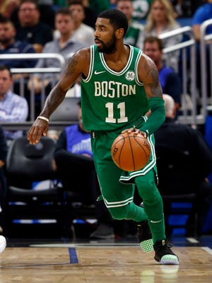 Boston Celtics guard Kyrie Irving (11) dribbles the ball against the Orlando Magic during the first quarter at Amway Center.