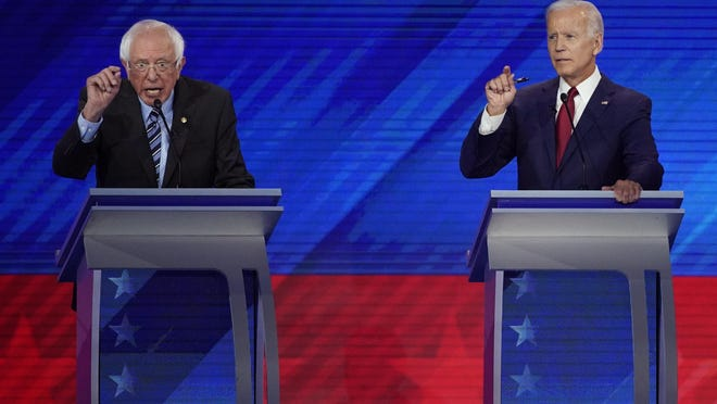 In this Sept. 12, 2019, photo, Sen. Bernie Sanders, I-Vt., left, and former Vice President Joe Biden, right, talk during a Democratic presidential primary debate hosted by ABC at Texas Southern University in Houston.