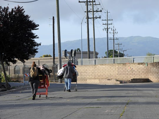 All alone on Market Way in Salinas, a homeless couple wheel their only possessions toward an uncertain future.