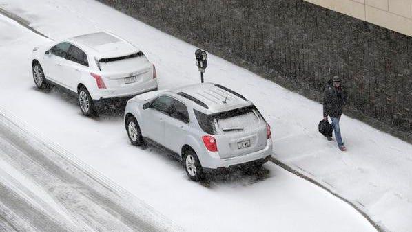 A pedestrian walks along Washington Street in Appleton as snow begins to blanket the area Tuesday.