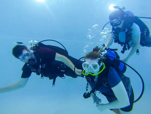 Caitlin Moffett scuba dives in the pool at DiVentures
