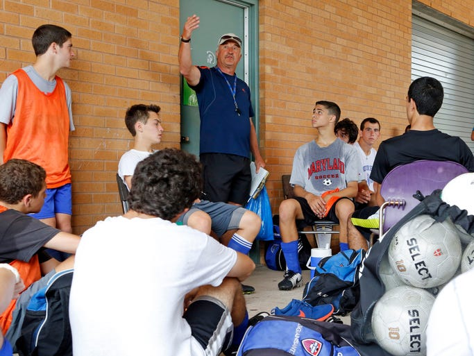 Blind Brook coach Jozef Pomoryn talks to his players during a water break at soccer practice, Aug. 21, 2014 in Rye Brook.