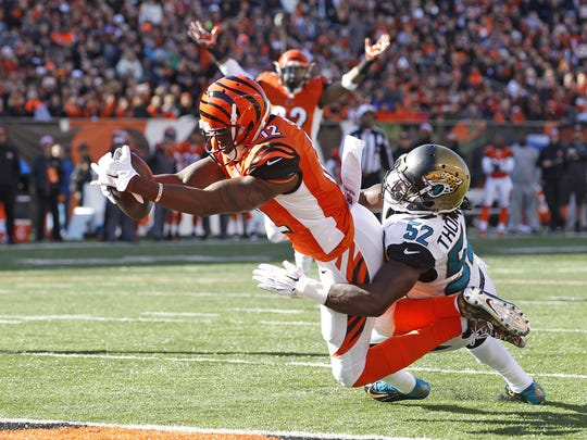 Cincinnati Bengals wide receiver Mohamed Sanu (12) dives int the end zone with a touchdown as Jacksonville Jaguars outside linebacker J.T. Thomas (52) attempts the tackle during the second quarter of their game played at Paul Brown Stadium in Cincinnati, Ohio Nov.  2, 2014.