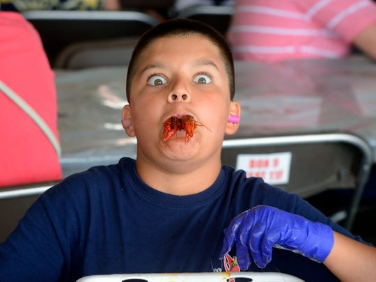 Aaron Rak, 11, has some crawfish during the 32nd annual Pensacola Crawfish Festival at Bartram Park. The festival returns Friday.