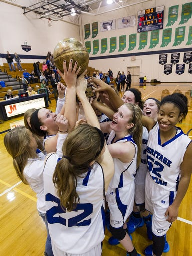 Heritage Christian players celebrate with their trophy after winning the 2014 City Girls Basketball Tournament championship game Friday, Jan. 17, 2014, at Cathedral High School. Heritage Christian defeated Bishop Chatard 65-51.