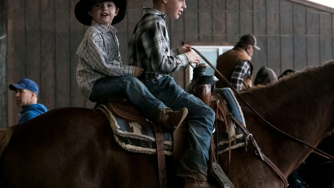 Grady Marks (left), 5, and his friend, Trulin Johnston, 9, ride the Johnston family horse Peanut at the Welcome Home Ranch in Gilbert on Saturday.