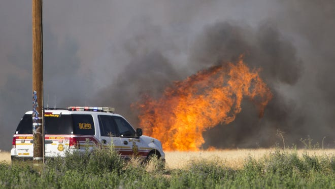 A Salt River firefighter monitors brush burning on the Salt River Reservation May 30, 2016.
