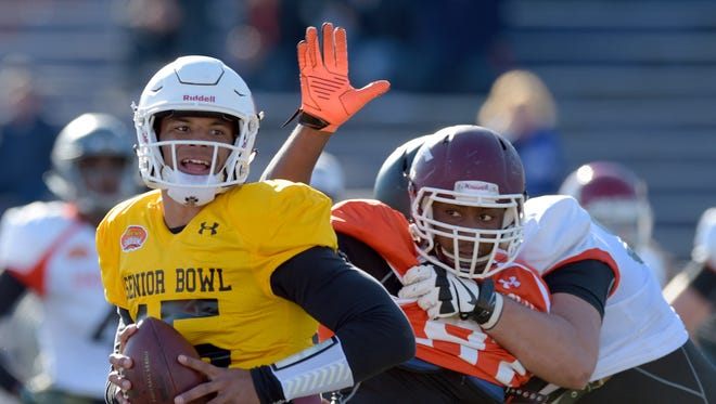 South squad quarterback Dak Prescott of Mississippi State (15) avoids the pressure of defensive end Noah Spence of Eastern Kentucky (97) during Senior Bowl practice at Ladd-Peebles Stadium.