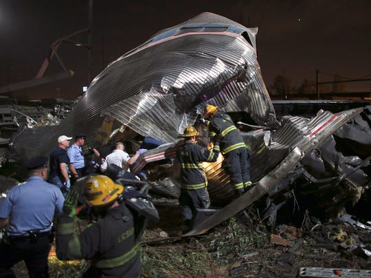 Emergency personnel work the scene of an accident, Tuesday, after an Amtrak train headed to New York City derailed and crashed in Philadelphia.