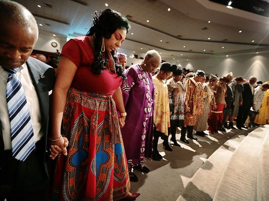 John Reese (left) and Wenela Malone gather with fellow church members at the altar during a special African-American history celebration at the New Sardis Baptist Church to honor living legends.