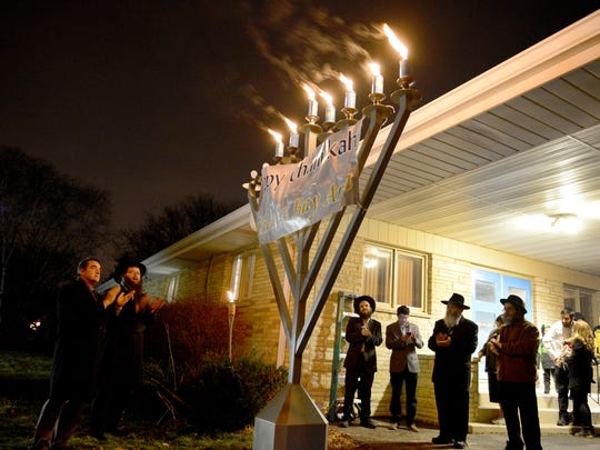 Green Bay Mayor Jim Schmitt, left, and Rabbi Michoel Feinstein lead a celebration after lighting candles on the menorah during Day 6 of Hanukkah on Sunday at Chabad of the Bay Area.